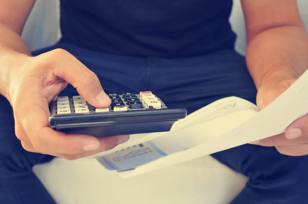 man with calculator doing payroll