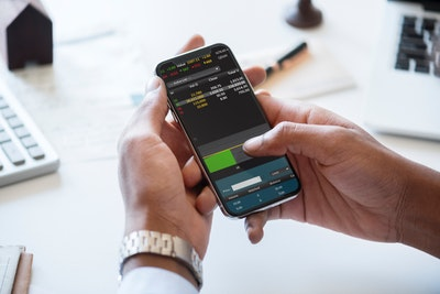 man looking at stock trading app on phone